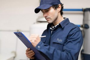 PURA installer checking items off his checklist
