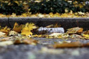 A plastic bottle in the gutter of a street