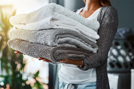 Someone carrying a stack of soft folded towels
