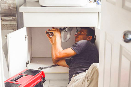 A plumber contorting body under sink to replace a rusted pipe