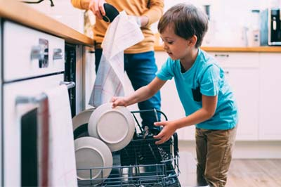 child helping parents unload the dishwasher
