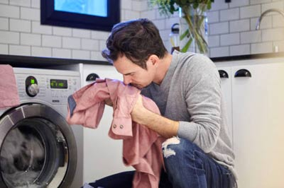 Person smelling fresh clothes after a wash
